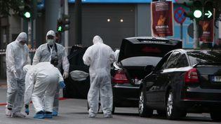 La police inspecte la voiture de l'ancien Premier ministre grec Lucas Papademos, blessé par une explosion, le 25 mai 2017 à Athènes. (ANGELOS TZORTZINIS / AFP)