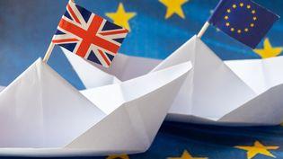 Deux bateaux en papier surmontés des drapeaux européen et britannique, le 20 juillet 2020. (RICCARDO MILANI / HANS LUCAS / AFP)