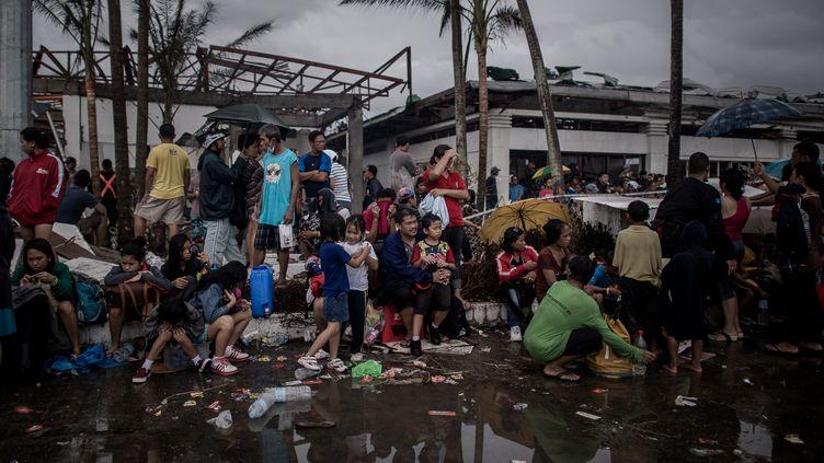 Des victimes du typhon Haiyan attendent d'être évacuées, à l'aéroport de Tacloban (Philippines), le 12 novembre 2013. (PHILIPPE LOPEZ / AFP)