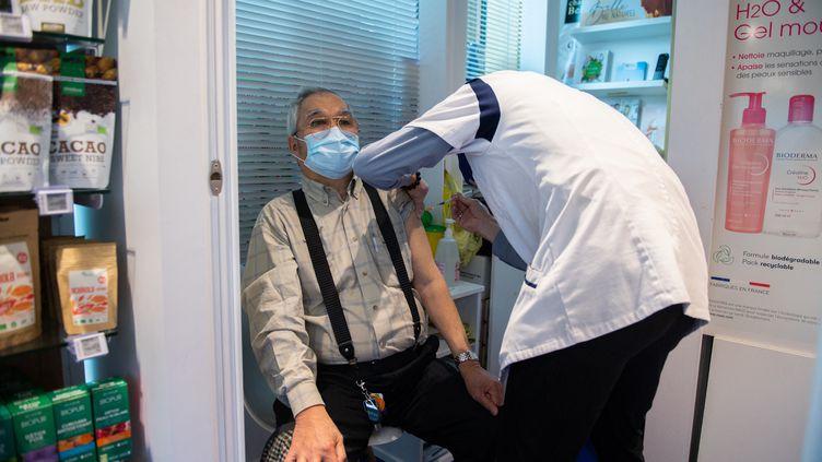 Un patient reçoit une injection du vaccin AstraZeneca, le 12 mars 2021, dans une pharmacie à Paris. (MARTIN BUREAU / AFP)