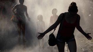 Des Parisiens se raffraichissent, le 20 juin 2019 à Paris Plage. (MANUEL COHEN / AFP)