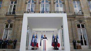 Emmanuel Macron, entouré par les ministres Florence Parly (à gauche) etGenevieve Darrieussecq (à droite), samedi 13 juillet 2019 à Paris. (KAMIL ZIHNIOGLU / AFP)