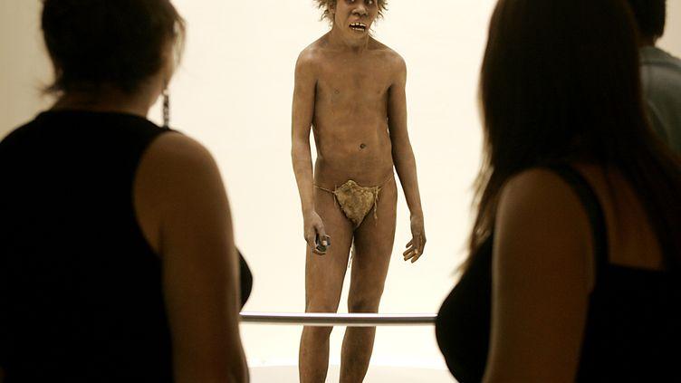 Des visiteurs observent la représentationd'un homme de Néandertal, le 19 juillet 2004 au musée national de la Préhistoire des Eyzies-de-Tayac (Dordogne). (PATRICK BERNARD / AFP)