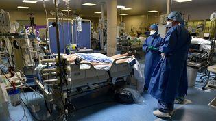 Des personnels hospitaliers face à un malade du Covid-19, en réanimation, à l'hôpital privé de Saint-Étienne (Loire), le 2 avril 2020. (REMY PERRIN / MAXPPP)