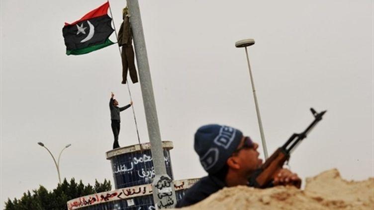Un insurgé surveille le ciel d'où pourraient être lancées des roquettes, à Ajdabiya le 15 mars 2011. (AFP - Roberto Schmidt)