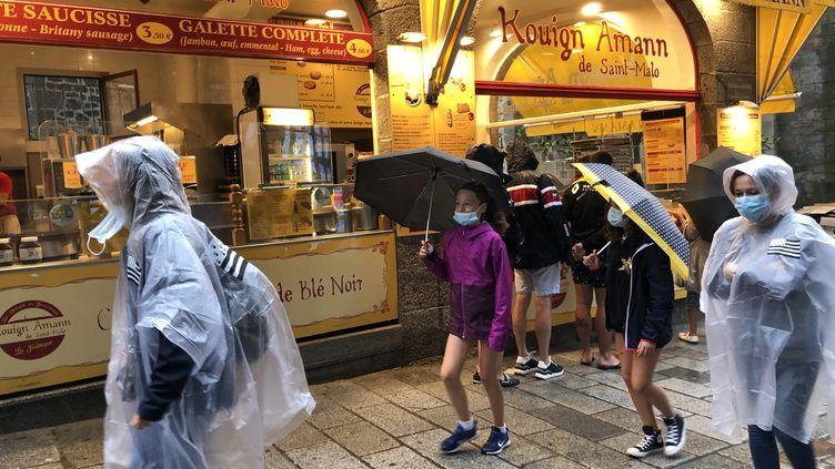 Des promeneurs affrontent la pluie à Saint-Malo (Ille-et-Vilaine), le 12 août 2020. (SANDRINE MULAS / HANS LUCAS / AFP)