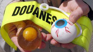 Un inspecteur des douanes pose avec des jouets dangereux, interdits de commercialisation en France depuis 2003, saisis à Saint-Nazaire (Loire-Atlantique)le 27 juin 2006. (FRANK PERRY / AFP)