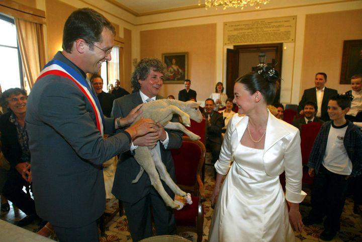 Jeune maire de Forcalquier (Alpes-de-Haute-Provence), Christophe Castaner (à gauche) offre un agneau de Provence à Raymond Manna, bassiste du groupe Trust, lors de son mariage, le 26 avril 2003. (MAXPPP)