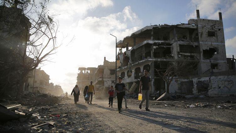 Des Palestiniens marchent dans les rues détruites, le 6 août 2014 à Gaza. (FINBARR O'REILLY / REUTERS)