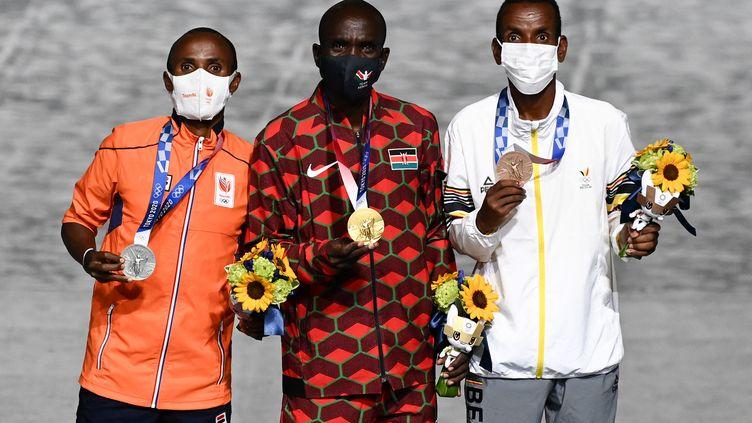 De gauche à droite, Abdi Nageeye (Pays-Bas), Eliud Kipchoge (Kenya) et Bashir Abdi (Belgique) sur le podium lors de la cérémonie deremise de médailles du marathon masculin, dans le cadre de la cérémonie de clôture des Jeux olympiques de Tokyo 2020, au stade olympique de Tokyo, le 8 août 2021. (JEWEL SAMAD / AFP)