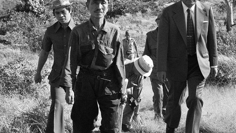 Cette image du vrai soldat de l'armée impériale japonaise, Hiroo Onoda, (au centre) a été prise le 11 mars 1974 quand on l'a retrouvé. Onoda est resté trois décennies caché dans la jungle, sur l'Ile de Lubang aux Philippines, parce qu'il croyait que la Seconde Guerre mondiale n'était pas terminée. Il est mort à Tokyo, à 91 ans, le 17 janvier 2014. (JIJI PRESS / JIJI PRESS / AFP)