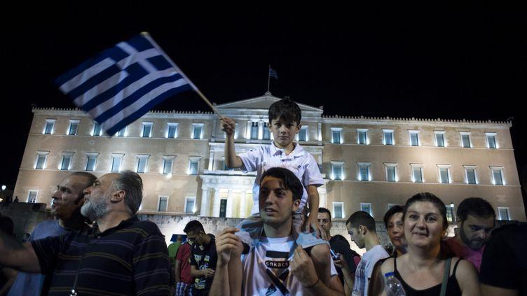 """Des Grecs célèbrent la victoire du """"non"""" au référendum sur l'avenir du pays, dimanche 5 juillet 2015 à Athènes. (IAKOVOS HATZISTAVROU / AFP)"""