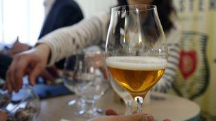 Une table de café avec un verre de bière à moitié plein. (FRANCOIS GUILLOT / AFP)