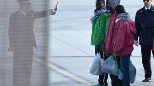 Un carabinieri donne ses instructions à des migrants avant leur embarquement sur l'aéroport de Lampedusa (Italie), le 17 février 2015. (ALBERTO PIZZOLI / AFP)