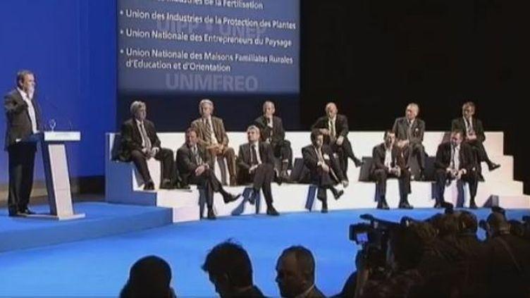 Nicolas Dupont-Aignan (debout à gauche), candidat à la présidentielle, expose son programme pour l'agriculture devant les membres de la FNSEA,à Montpellier (Hérault) jeudi 29 mars 2012. (CAPTURE D'ÉCRAN FTVI / FRANCE TÉLÉVISIONS )
