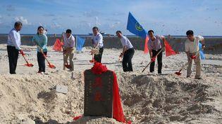 Cérémonie de pose de la première pierre pour la construction de deux phares sur le récif de Huayang (Cuarteron) en mer de Chine, en présence du ministre chinois des transports, le 26 mai 2015, pour sécuriser la navigation. (Lu Rui/XINHUA/AFP)