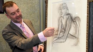"""Patrice Deparpe, directeur du Musée Matisse du Cateau-Cambrésis (Nord), presente un dessin d'Henri Matisse, """"La femme accoudee"""",de l'exposition """"Devenir Matisse"""", visible jusqu'au 9 février 2020.. (FRANCOIS LO PRESTI / AFP)"""
