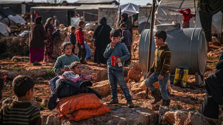 Des volontaires d'une association distribuent de l'aide à des Syriens qui vivent dans des camps de réfugiés, le 23 janvier 2021 àIdlib, en Syrie. (MUHAMMED SAID / ANADOLU AGENCY / AFP)