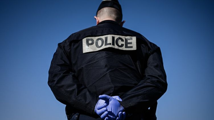 Un policier avec des gants de protection pendant l'épidémie de coronavirus le 24 mars 2020 à Paris. (PHILIPPE LOPEZ / AFP)