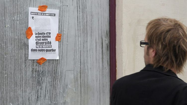 """Une affichette défendant la diversité du quartier de la Goutte d'or et dénonçant l'""""apéro saucisson"""" (AFP/BERTRAND LANGLOIS)"""
