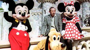 Le neveu de Walt Disney, Roy Disney, entouré de Mickey, Minnie et Pluto, lors de l'inauguration de Disneyland à Marne-la-Vallée (Seine-et-Marne), le 11 avril 1992. (ERIC FEFERBERG / AFP)
