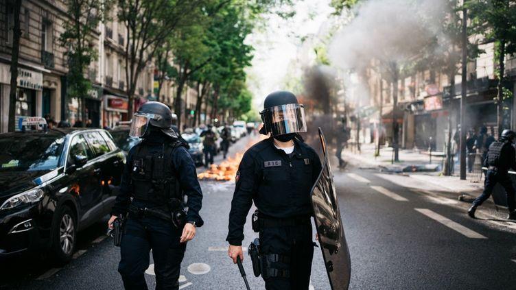 Deux policiers devant une poubelle en feu, le 15 mai 2021 à Paris lors d'une manifestation en soutien à la Palestine. (XOSE BOUZAS / HANS LUCAS / AFP)