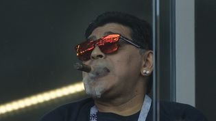 Diego Maradona savoure un cigare dans une tribune non-fumeur du stade du Spartak Moscou, le 16 juin 2018 lors du match Argentine-Islande. (JUAN MABROMATA / AFP)
