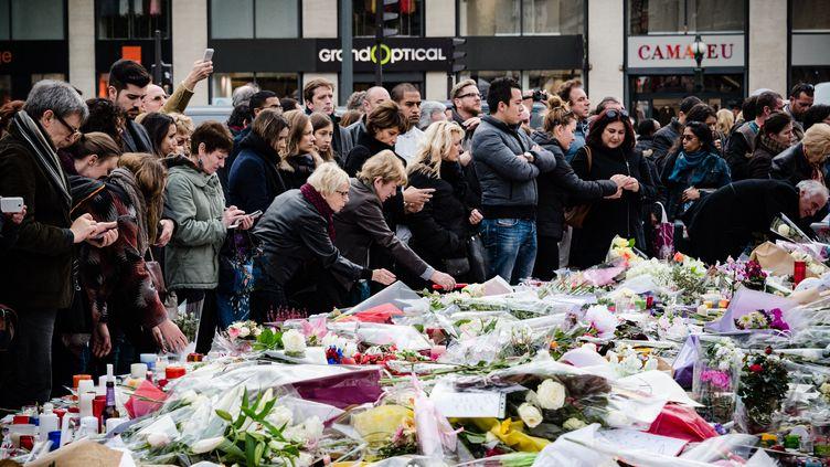 16 novembre 2015, Paris. Trois jours après les attaques du 13 novembre 2015, des dizaines de personnes rendent hommage aux victimes des attentats qui ont tué 130 personnes, avec des fleurs, des bougies et des messages au pied de la statue de la République. (Illustration) (SAMUEL BOIVIN / NURPHOTO VIA AFP)