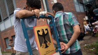 (Des demandeurs d'asile devant le bureau des migrants et réfugiés à Berlin © Reuters-Stefanie Loos)