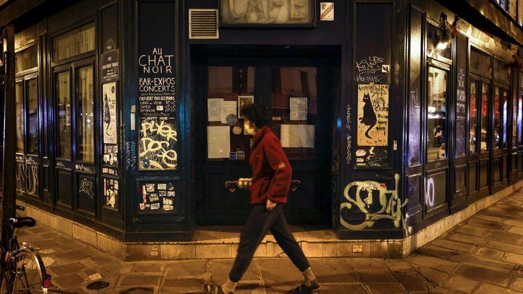 Une femme passe devant un café fermé dans le 11e arrondissement de Paris, le 6 octobre 2020. (THOMAS COEX / AFP)