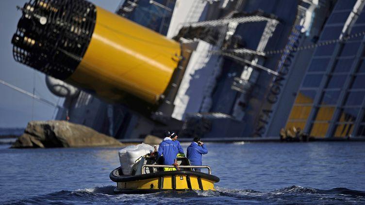"""Des techniciens longent l'épave du """"Concordia"""", le 26 janvier 2012 près de l'île du Giglio (Italie). (FILIPPO MONTEFORTE / AFP)"""