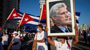 Une femme brandit un portrait du président cubain MiguelDiaz-Canel lors d'un meeting à La Havane le 17 juillet 2021. (YAMIL LAGE / AFP)