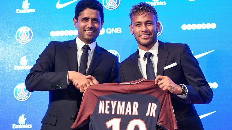L'attaquant brésilien Neymar (à droite) pose avec le président du PSG,Nasser Al-Khelaifi, à Paris, le 4 août 2017. (LIONEL BONAVENTURE / AFP)