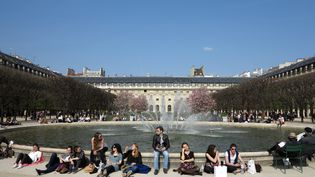 Des Parisiens profitent des températures exceptionnellement clémentes au jardin du Palais-Royal, le 26 mars 2017. (LUDOVIC MARIN / AFP)