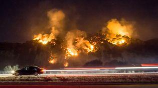"""Aidé par des vents qui ont augmenté de manière spectaculaire, atteignant 130 km/h sur les hauteurs, les incendies continuaient de se propager au soir du 6 décembre 2017, comme ici l'incendie """"Thomas"""", le long d'une route à Casitas Springs, au nord-ouest de Los Angeles. (KYLE GRILLOT / AFP)"""