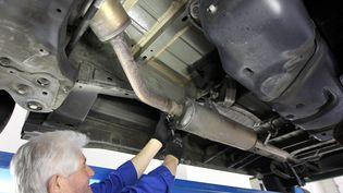 Un garagiste bordelais démonte un pot catalytique, en mars 2013. ( MAXPPP)