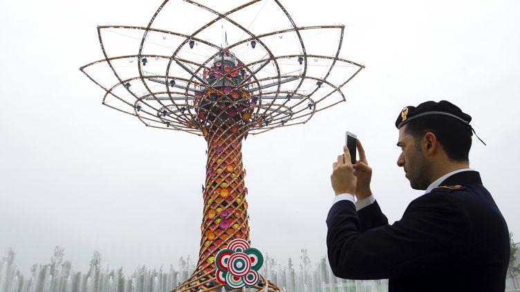 """Un policier photographie """"l'Arbre de la vie"""", une structure architecturale de l'Expo universelle, le 1er mai 2015. (ALESSANDRO GAROFALO / RE)"""