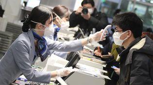 Une employée prend la température d'un passager lors du check-in avant un vol pour Wuhan, le 31 janvier 2020à l'aéroport Haneda de Tokyo (Japon). (MASAMINE KAWAGUCHI / YOMIURI / AFP)