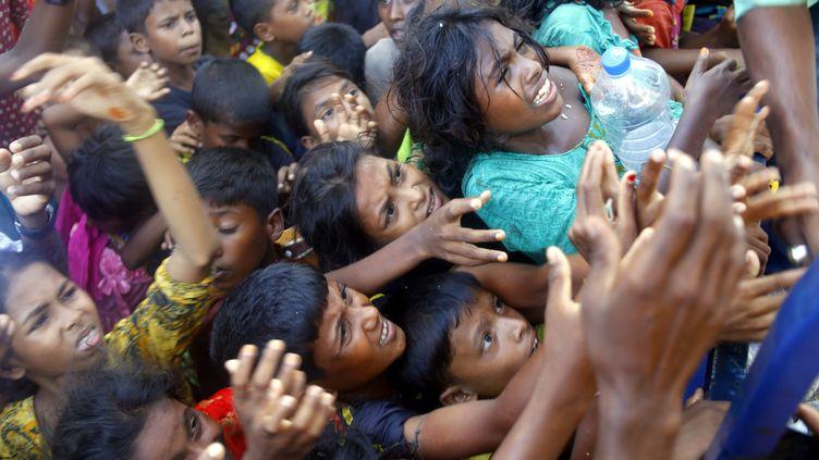 Des réfugiés Rohingyas, le 15 septembre 2017,autour d'un camion livrant des vêtements à Ukhia, au Bengladesh. (SONY RAMANY / NURPHOTO / AFP)