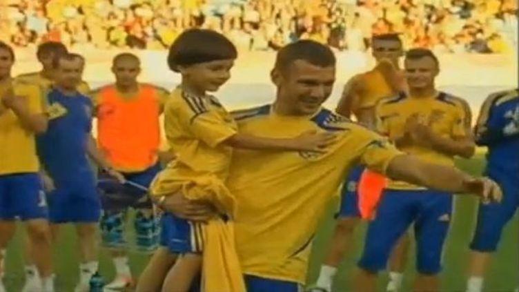 Le petit garçon, Timour Chamanov dans les bras dede son idole Andreï Shevchenko à Donestk (Ukraine) jeudi 14 juin 2012