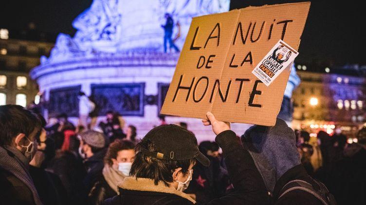 """Un manifestant tenant une pancarte sur laquelle il est écrit """"La nuit de la honte"""" sur la place de la Républiquele 24 novembre pour dénoncer l'évacuation violente d'un camp de migrants lundi. (SAMUEL BOIVIN / NURPHOTO / AFP)"""