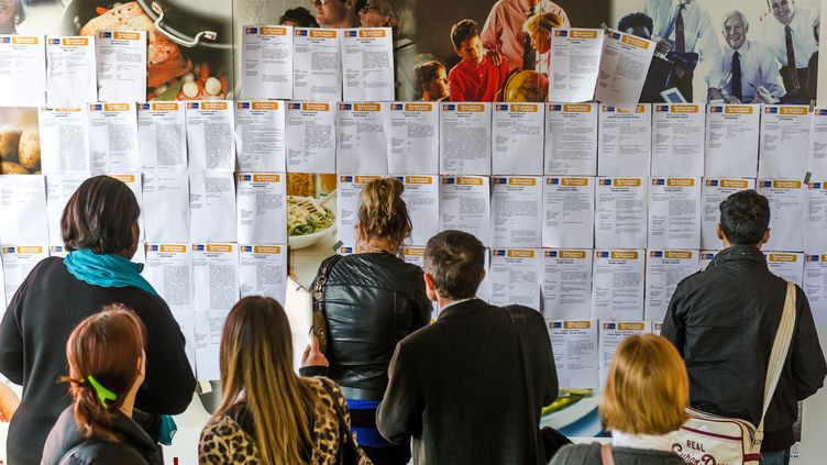 Des demandeurs d'emploi consultent les annonces affichées au mur d'une agence Pôle emploi, à Lens (Pas-de-Calais), le 17 avril 2014. (PHILIPPE HUGUEN / AFP)