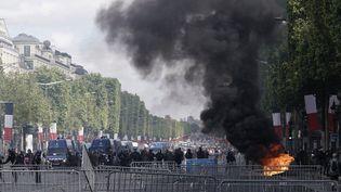 Une poubelle en feu sur l'avenue des Champs-Elysées, à Paris, le 14 juillet 2019. (KENZO TRIBOUILLARD / AFP)