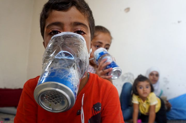 Des enfants essaient des masques à gaz bricolés avec des canettes, dans la province d'Idleb (Syrie), le 12 septembre 2018. (MUHAMMAD HAJ KADOUR / AFP)