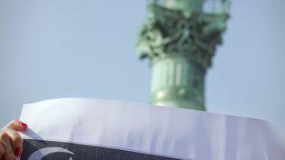 Une manifestante tient une affiche avec les symboles des différentes religions à Paris, en mars 2012. (JOEL SAGET / AFP)