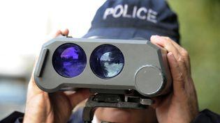 Un policier effectue, à l'aide d'un radar, des contrôles de vitesse, sur les quais de Bordeaux, le 29 octobre 2011. (JEAN-PIERRE MULLER / AFP)