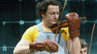 """Coluche enregistre un sketch musical pour l'émission """"Numéro un"""" (1977). (JACQUES CHEVRY / Ina / AFP)"""