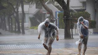 Des habitants de Naha, sur l'île d'Okinawa (Japon) tentent d'éviter la pluie et les vents violents du typhon Vongfong, le 11 octobre2014. (KYODO / REUTERS )