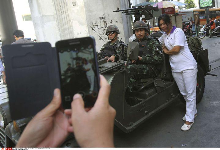Une Thaïlandaise pose avec des militaires, à Bangkok (Thaïlande), le 20 mai 2014. (SAKCHAI LALIT / AP / SIPA)