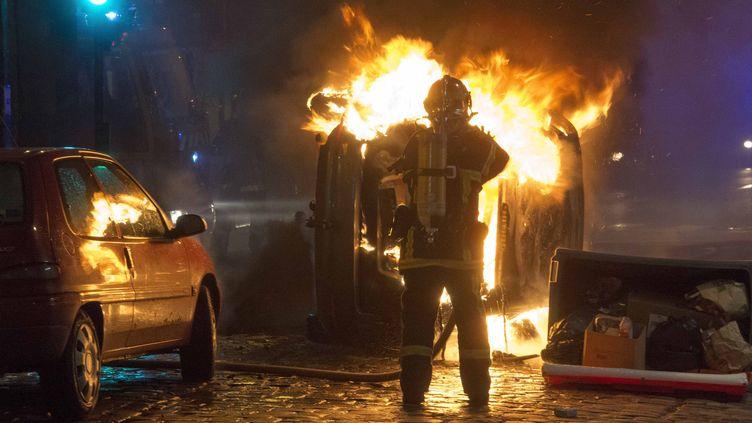 Un pompier intervient sur un incendie, après des incidents lors d'une manifestation anti-FN, le 8 février 2014, à Rennes (Ille-et-Vilaine). ( MAXPPP)